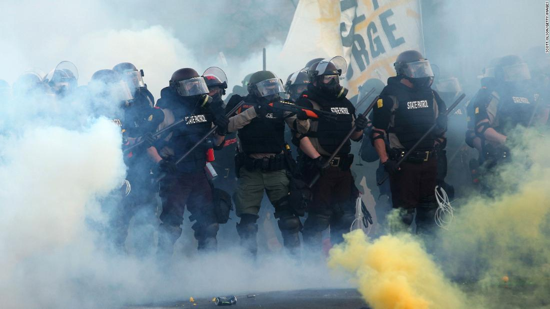 Police advance through smoke and tear gas toward demonstrators in Minneapolis on Saturday.
