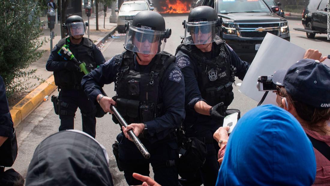Police hold back demonstrators in the Fairfax District of Los Angeles on Saturday, May 30.