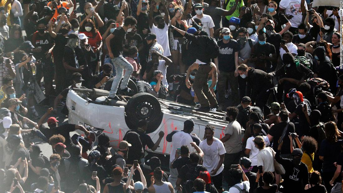 Protesters jump on an overturned car near the Municipal Services Building in Philadelphia on Saturday.