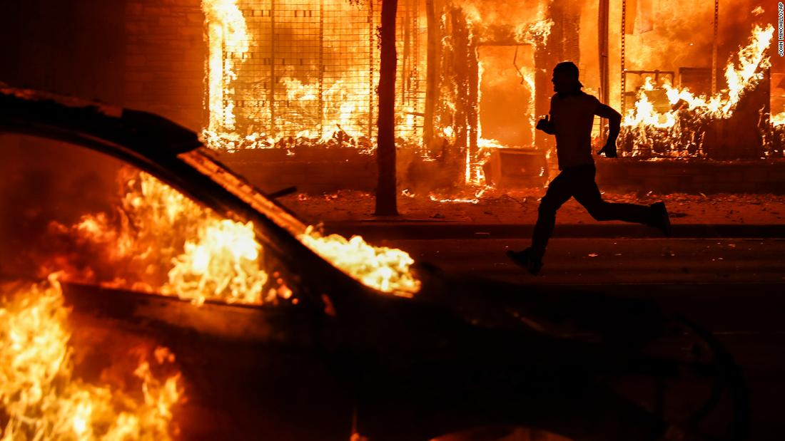 A protester runs past burning cars and buildings on Chicago Avenue, on May 30 in St. Paul, Minnesota.