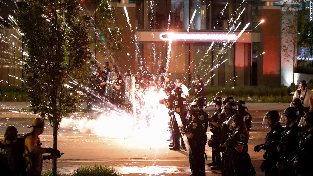 A firework explodes by a police line on May 30 near the White House in Washington.