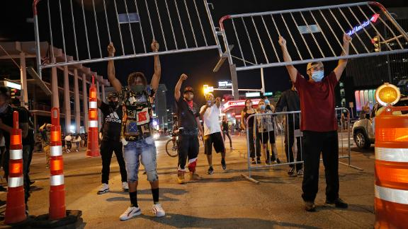 Protesters hold up metal gates as they build a barrier in a roadway on Saturday, May 30, in Las Vegas.