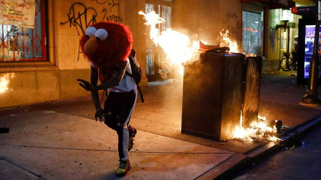 A protester in an Elmo mask dances as a fire burns in Philadelphia on May 30.