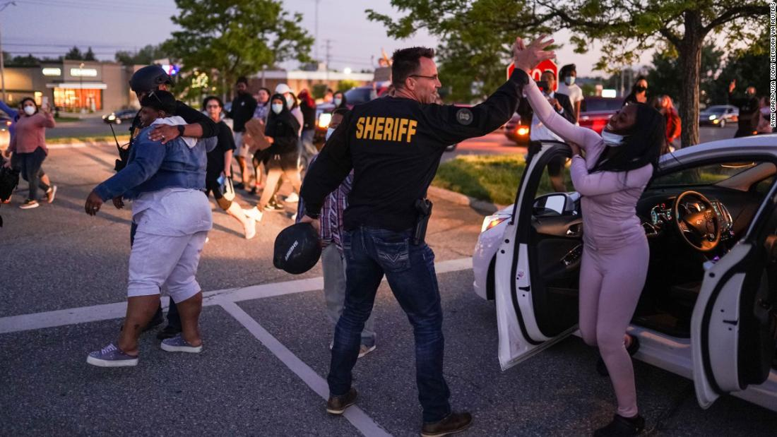 Genesee County Sheriff Chris Swanson high fives a woman who called his name as he marches with protesters in Flint, Michigan, on May 30.