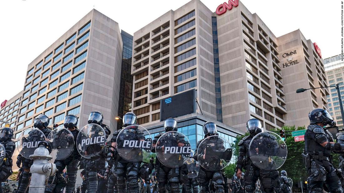 Police stand guard near CNN Center and Centennial Olympic Park as protests continue on Saturday in Atlanta.