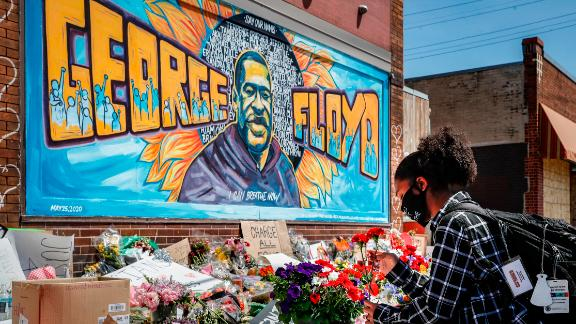 Malaysia Hammond, 19, places flowers at a memorial mural for George Floyd at the corner of Chicago Avenue and 38th Street, Sunday, May 31, 2020, in Minneapolis. Protests continued following the death of George Floyd, who died after being restrained by Minneapolis police officers on Memorial Day. (AP Photo/John Minchillo)