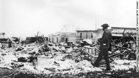After the Tulsa riot in 1921, an African American looked at the skeleton of the iron bed with a camera. The iron skeleton rose from the burnt soot.