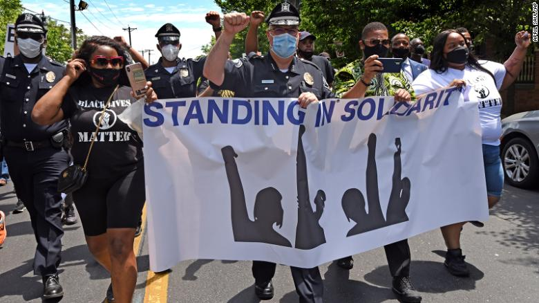 Camden County Metro Police Chief Joe Wysocki raises a fist while participating in a solidarity March Saturday.