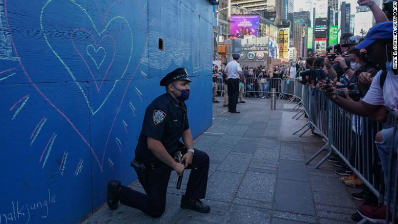 A New York City police officer takes a knee during a demonstration by protesters in Times Square.