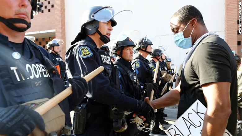 A demonstrator and police officer shake hands in Kansas City, Missouri.