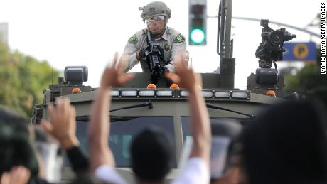 A police officer aims a nonlethal weapon as protesters raise their hands during demonstrations in Santa Monica, California, on May 31.