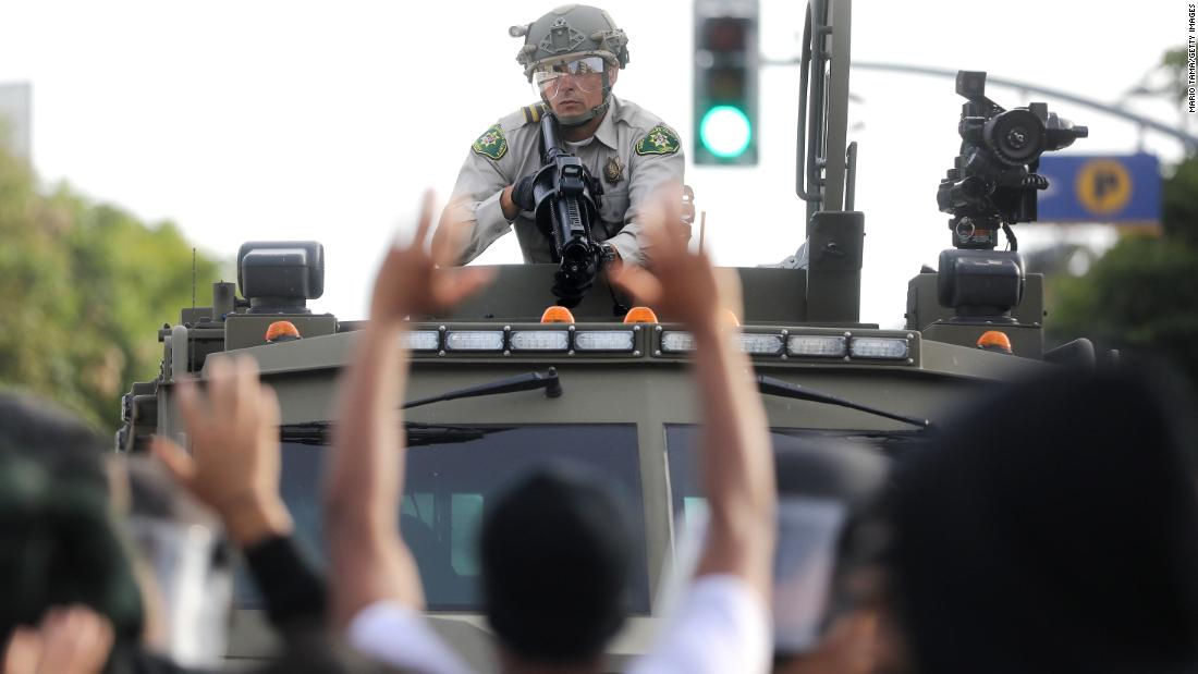 A police officer aims a nonlethal weapon as protestors raise their hands during demonstrations on May 31 in Santa Monica, California.