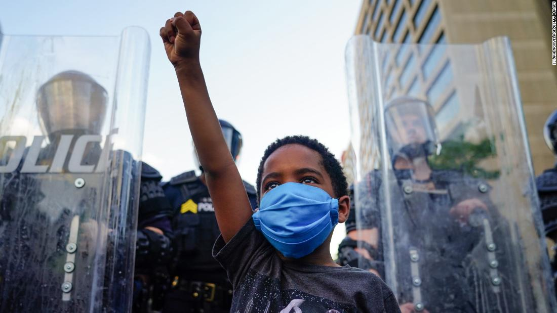 A young boy raises his fist for a photo by a family friend during a demonstration on May 31 in Atlanta.