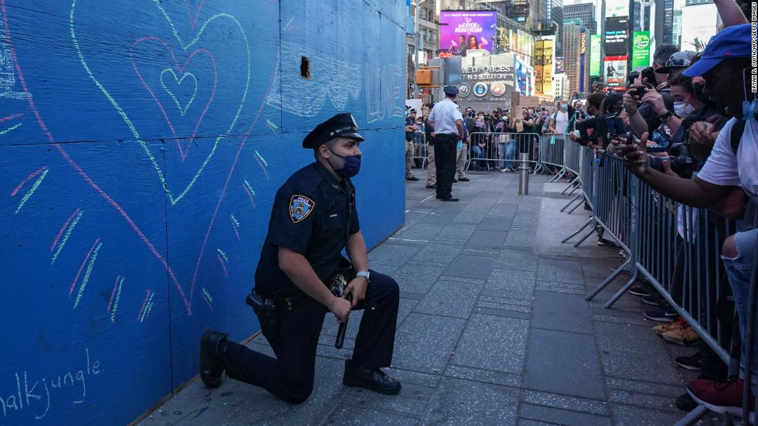 A New York City police officer takes a knee during a demonstration by protesters in Times Square at a rally on May 31 in New York.