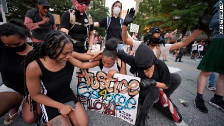 Demonstrators stopped to pray during a protest in Atlanta Friday.