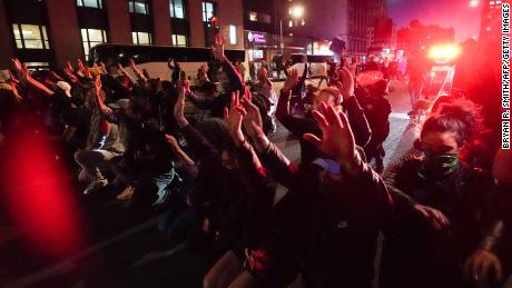 Protesters take a knee and raise their hands in the middle of New York's Canal Street on May 31 in a standoff with police over the death of George Floyd.