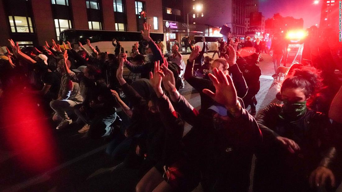 Protesters take a knee and raise their hands in the middle of Canal Street in a stand off with police at a rally on May 31 in New York.