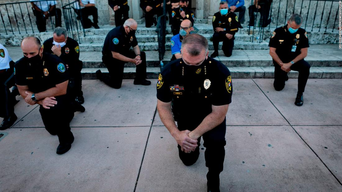 Police officers kneel during a rally in Coral Gables, Florida, on May 30, 2020 in response to the death of George Floyd.