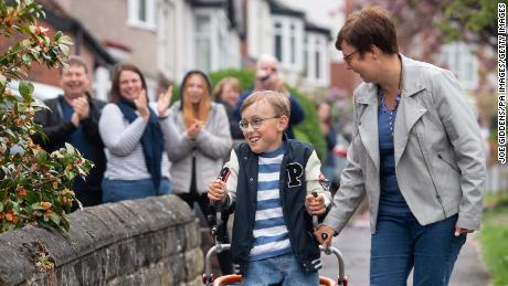 Tobias is cheered on by neighbors as he walks along his street in Sheffield, northern England.