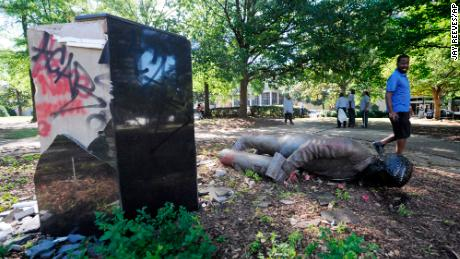 An unidentified man walks past a toppled statue of Charles Linn, a city founder who was in the Confederate Navy, in Birmingham, Ala., on Monday, June 1, 2020, following a night of unrest.