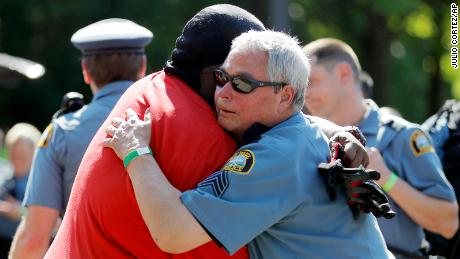 A protester and an officer hug.