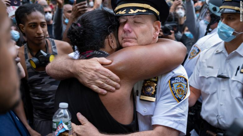 Chief of Department of the New York City Police, Terence Monahan, hugs an activist.