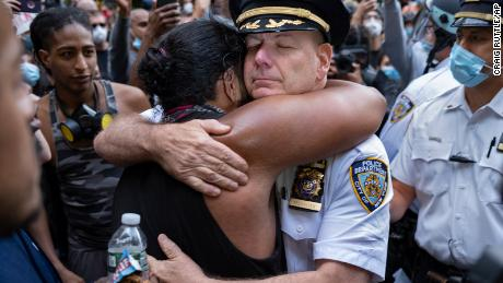 New York Police Department chief Terence Monahan hugs an activist.