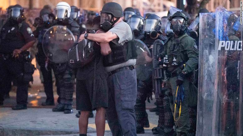 An officer clad in a helmet and mask hugs a protester.