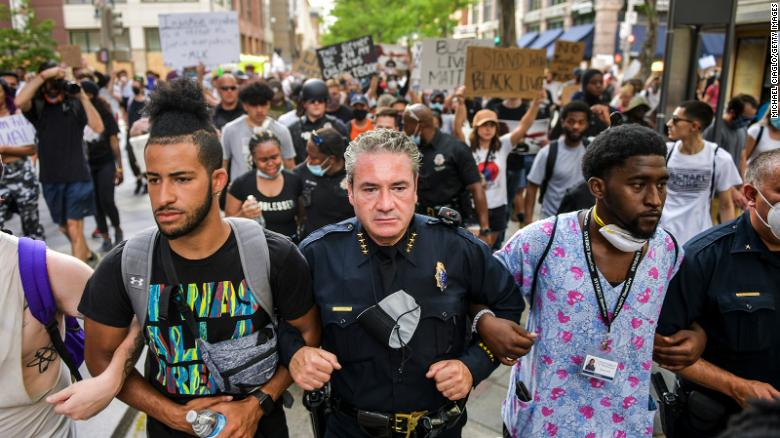 Denver Police Chief Paul Pazen links arms with people protesting.