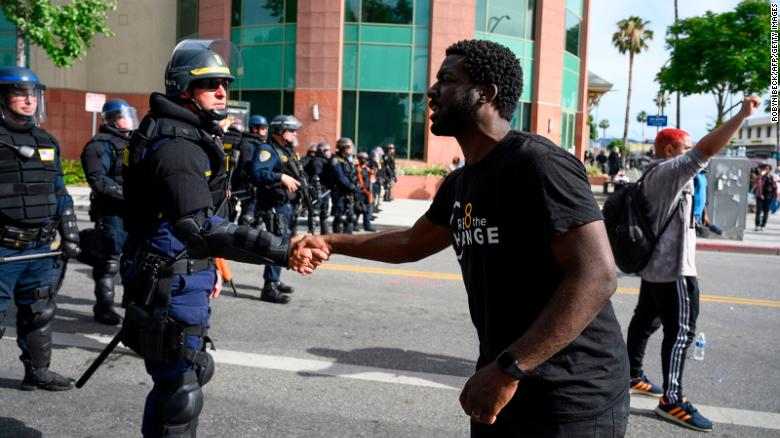 A CHP officer and protester shake hands during a demonstration.