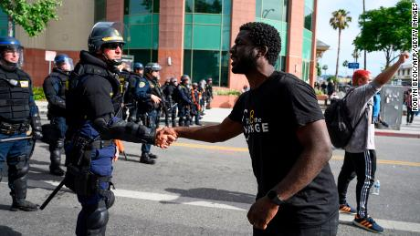 A CHP officer and a protester shake hands during a demonstration.