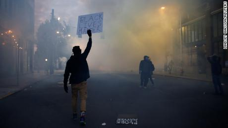 "A person holds a ""Black Lives Matter"" sign as as a heavy cloud of tear gas and smoke rises after being deployed by Seattle police as protesters rally against police brutality and the death in Minneapolis police custody of George Floyd, in Seattle, Washington, U.S. June 1, 2020. REUTERS/Lindsey Wasson"