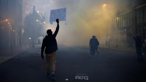 """A person holds a """"Black Lives Matter"""" sign as as a heavy cloud of tear gas and smoke rises after being deployed by Seattle police as protesters rally against police brutality and the death in Minneapolis police custody of George Floyd, in Seattle, Washington, U.S. June 1, 2020. REUTERS/Lindsey Wasson"""