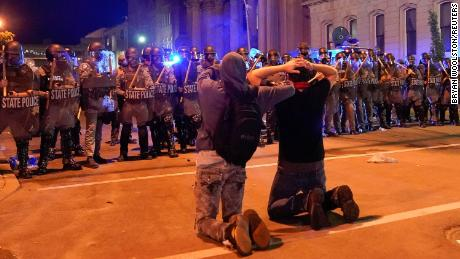 Two men kneel in front of a line of Kentucky State Troopers during a June 1 protest in Louisville, Kentucky.