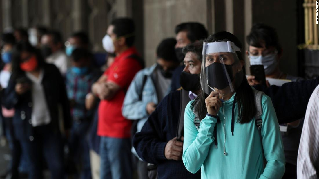 People wearing masks wait for the mayor's office to open in Mexico City, Monday, June 1.