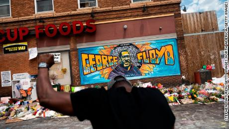MINNEAPOLIS, MN - JUNE 01: A man kneels and holds up his fist at a memorial site where George Floyd died May 25 while in police custody, on June 1, 2020 in Minneapolis, Minnesota. George's brother Terrence Floyd visited the site today and called for justice and the prosecution of all four officers involved in the incident. (Photo by Stephen Maturen/Getty Images)