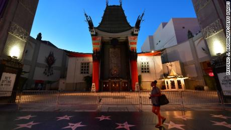 A woman walks past the closed courtyard in front of the TCL Chinese Theater, famed for the hand and foot prints of movie stars.