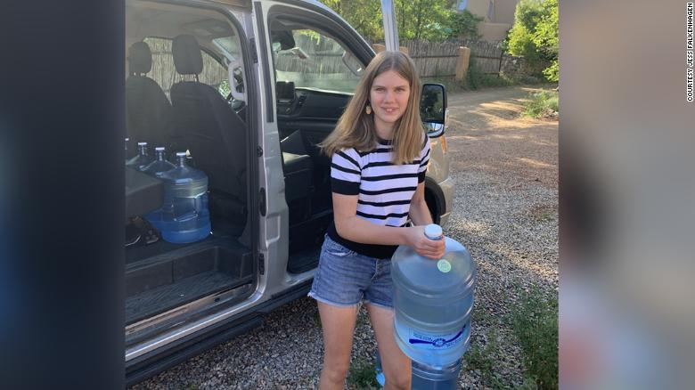 Daisy Russell loading water jugs into the van. The water would soon be delivered to the Navajo nation in Window Rock, Arizona.