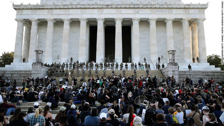 Members of the D.C. National Guard stand on the steps of the Lincoln Memorial monitoring a large crowd of demonstrators participating in a peaceful protest against police brutality and the death of George Floyd.