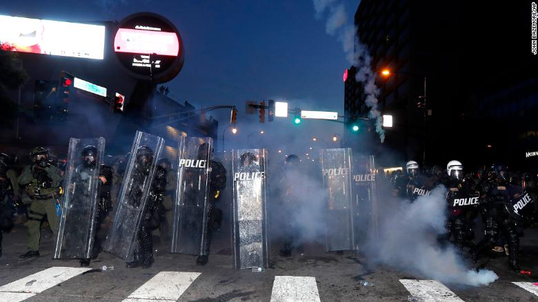 Atlanta police prepare to enforce a 9:00 pm curfew with gas as demonstrators chant, Tuesday.