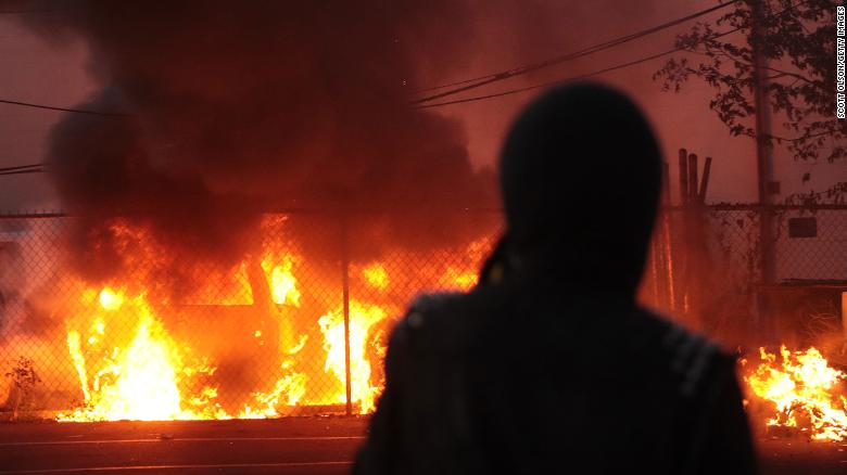 A person in Minneapolis, Minnesota watches vehicles burn during a May 29 protest sparked by the death of George Floyd.