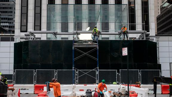 Workers put up boards around the Apple flagship store on Fifth Avenue, after a night of protest over the death of George Floyd in Minneapolis.