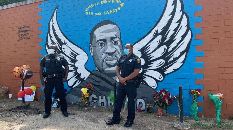 Two Houston police officers visit a memorial for George Floyd to pay their respects.