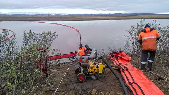 Members of the Marine Rescue Service work near the spill on Wednesday.
