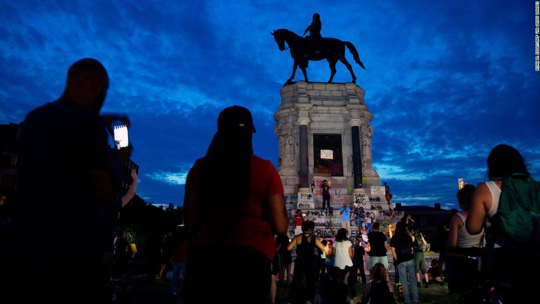 CNN has blurred expletives written on the base of the statue. People gather around the Robert E. Lee statue on Monument Avenue in Richmond, Virginia, on June 4, calling for its removal amid continued protests over the death of George Floyd in police custody.