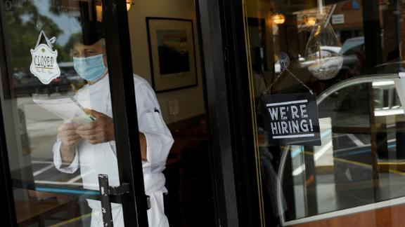 """A """"We're Hiring"""" sign advertising jobs is seen at the entrance of a restaurant, as Miami-Dade County eases some of the lockdown measures put in place during the coronavirus disease (COVID-19) outbreak, in Miami, Florida, U.S., May 18, 2020. Photo by Marco Bello/Reuters"""
