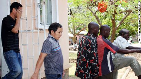 Wu Jiu Hua (L) and Xiao Li Shan (C), the two Chinese managers alleged to have shot 12 workers at Collum coal mine, leave the Choma Magistrate Court with other Zambian suspects on November 2, 2010 in Sinazongwe.