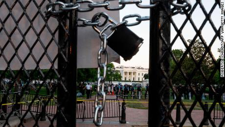 A locked padlock keeps a metal fence recently erected in front of the White House and meant to keep protestors at bay closed on June 2, 2020. (Photo by ROBERTO SCHMIDT/AFP via Getty Images)