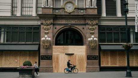 NEW YORK, NY - JUNE 02: A person rides by the Macy's flagship store after workers cleaned and boarded up damage sustained during a night of violent protests and looting in Midtown, Manhattan on June 2, 2020 in New York City. In spite of a police-enforced 11pm curfew, dozens of shops were ransacked during the  previous evening's violent clashes between the NYPD and protesters demanding justice for George Floyd, an unarmed black man killed by law enforcement in Minneapolis on May 25th. (Photo by Scott Heins/Getty Images)