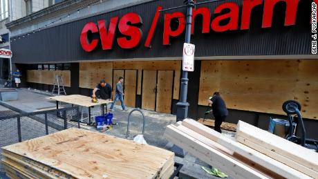 Windows broken in a downtown Pittsburgh CVS Pharmacy are repaired Sunday, May 31, 2020. The damage was done a during a march in Pittsburgh, Saturday, May 30, 2020 to protest the death of George Floyd, who died after being restrained by Minneapolis police officers on Memorial Day, May 25. (AP Photo/Gene J. Puskar)